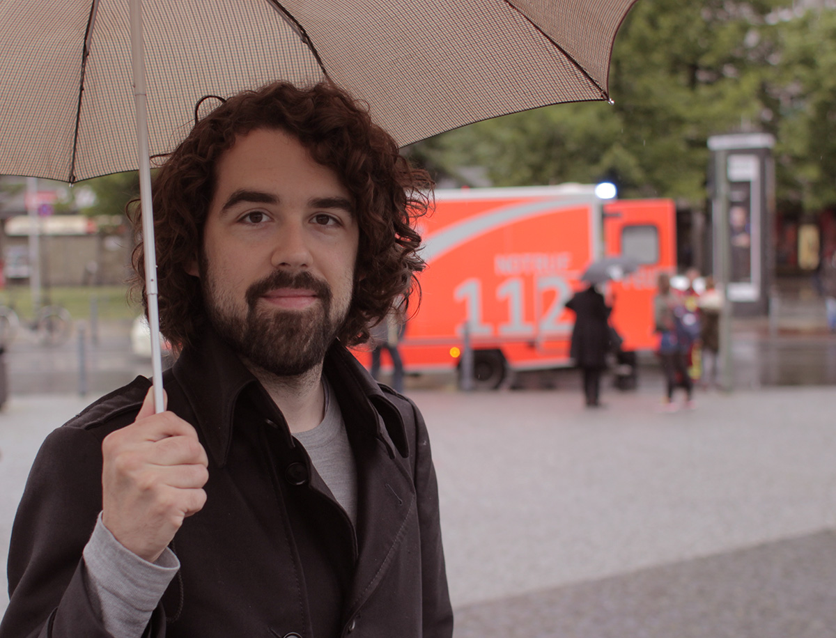 Autor, im Regen stehen gelassen. Mit Regenschirm.